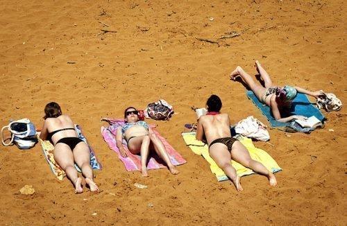 Люди на пляже загорают